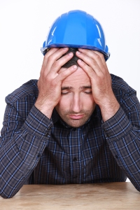 construction builder holding his head in his hands looking worried