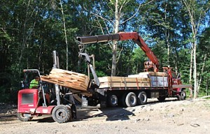 working together to using Moffatt to move rafters from the truck to the crane of the boom truck