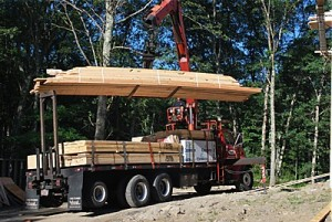 Bundle of pre cut rafters being lifted off boom truck to be placed on rooftop