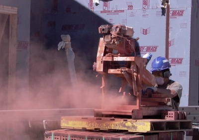construction worker sawing dry brick releasing dust containing silica